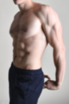 Muscular male torso of bodybuilder on wh
