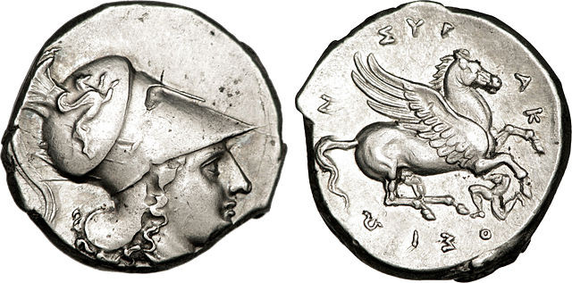 Moeda de ouro ou de prata usada na Grécia Antiga. No cristianismo, moeda de ouro que correspondia a 4 dracmas, usada para o pagamento de impostos.