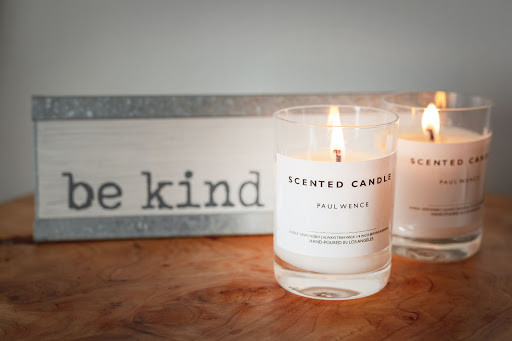 Two candles in white glasses with a be kind sign behind them.
