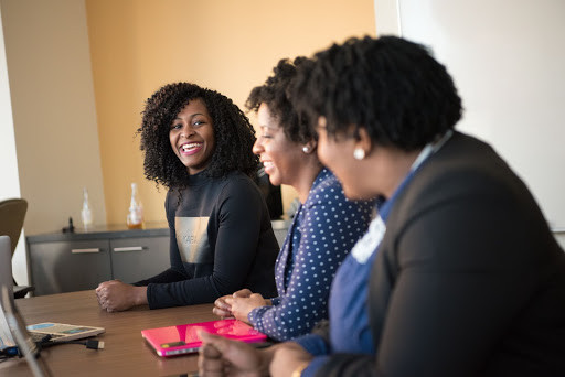 Three Black women laughing in an office setting.