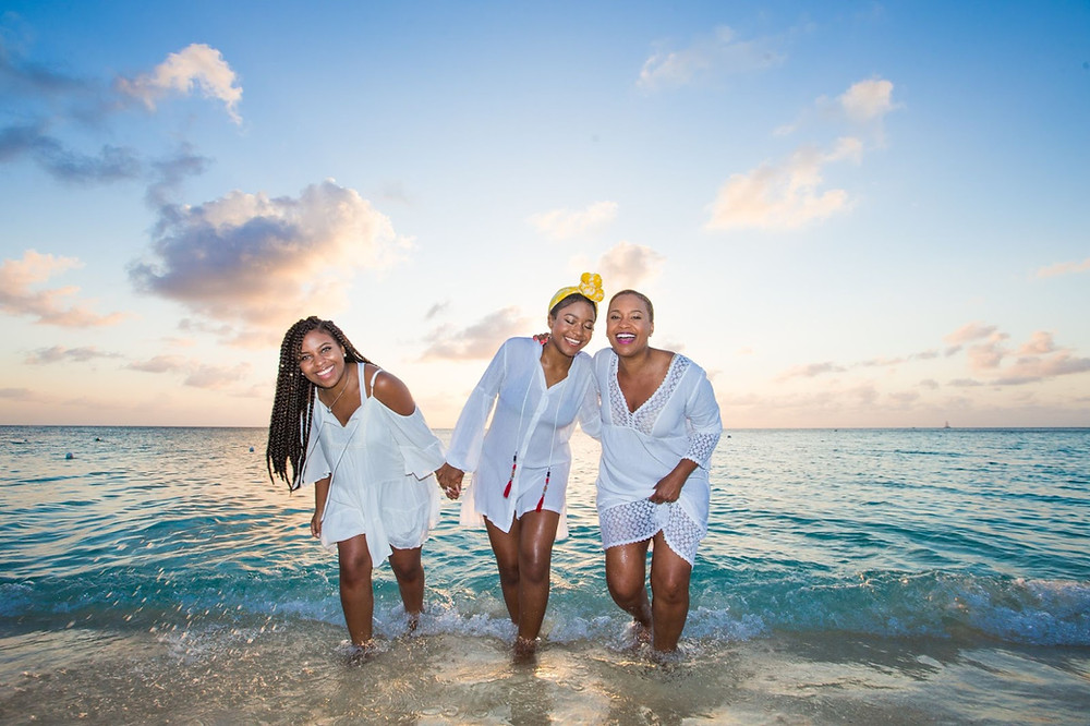 Three Black women in white embrace one another while at the beach.