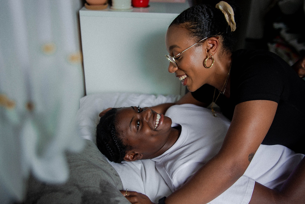 African American queer couple smiling in bed