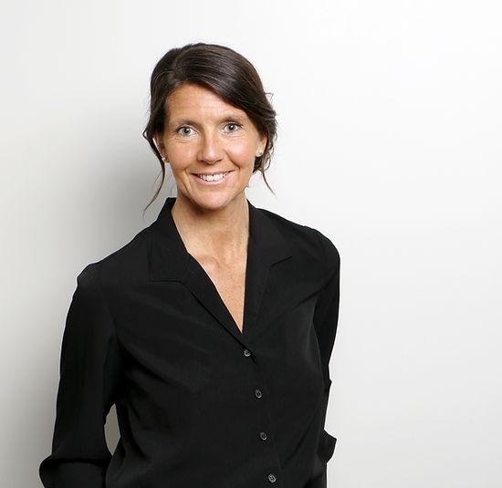 Photo de Karine Thellier souriante et professionnelle. Elle est habillée d'une blouse classique de couleur noir sur un fond pastel.