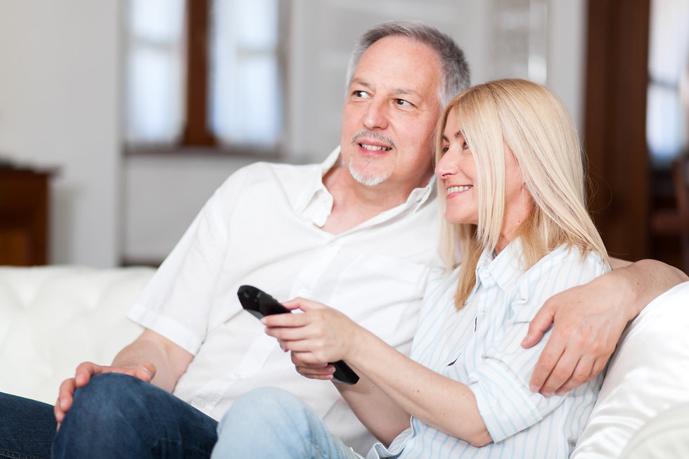 Portrait of a mature couple watching tel