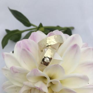 Gelijke geelgouden, gehamerde trouwringen met roosgeslepen diamant.