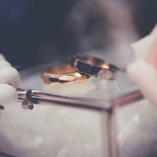 Geelgouden gefaceteerde trouwring voor haar. Hij een zwaardere gehamerde band met glazende zijdes.