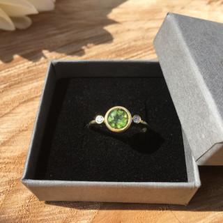 Fijne geelgouden verlovingsring met peridoot, geflankeerd door twee achtkant diamanten.