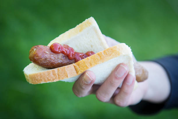 Woman holding a cooked sausage on white bread