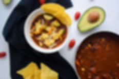 Vegetarian chili with avocado and chips.