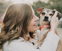 smiling-woman-carrying-dog-near-tree