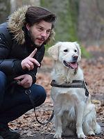 Man kneeling next to his Golden Retriever dog on an outdoor hike