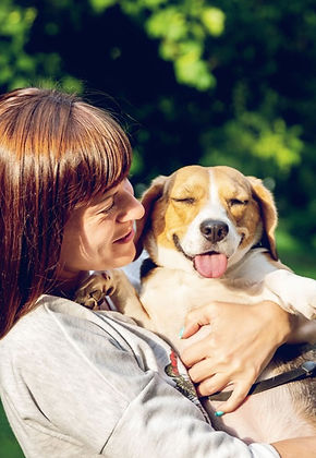 Woman in grey long sleeved shirt holding her Bhappy Beagle dog in the sunshine