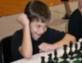 kid playing chess in tournament