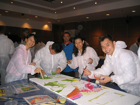 An enthusiastic team painting their image during a team building event by Sabre