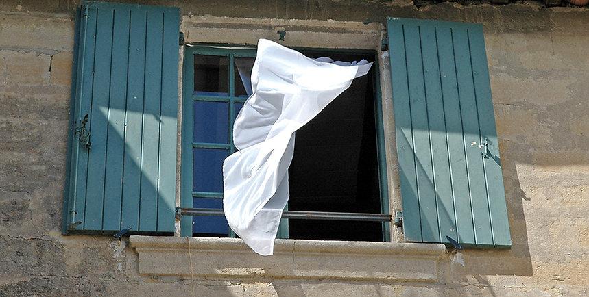Rideau d'une fenêtre gonflé par le vent à Uzès