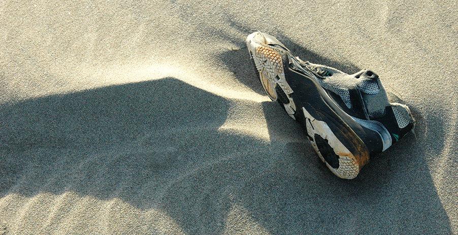 une basket abandonnée su le sable de la plage
