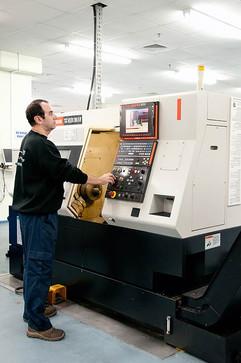 צילום תעשייתי של עובד לייד מכונת חריטה