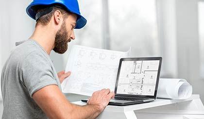 פועל באתר בודק תוכניות בנייה