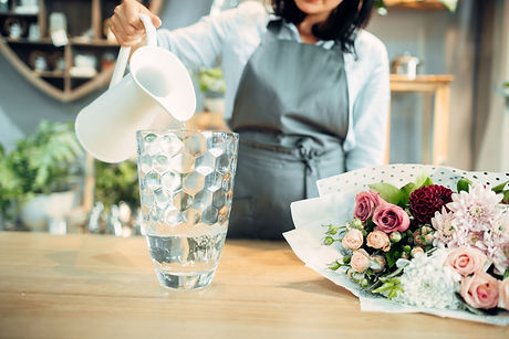 Florist pours water into a vase in flowe