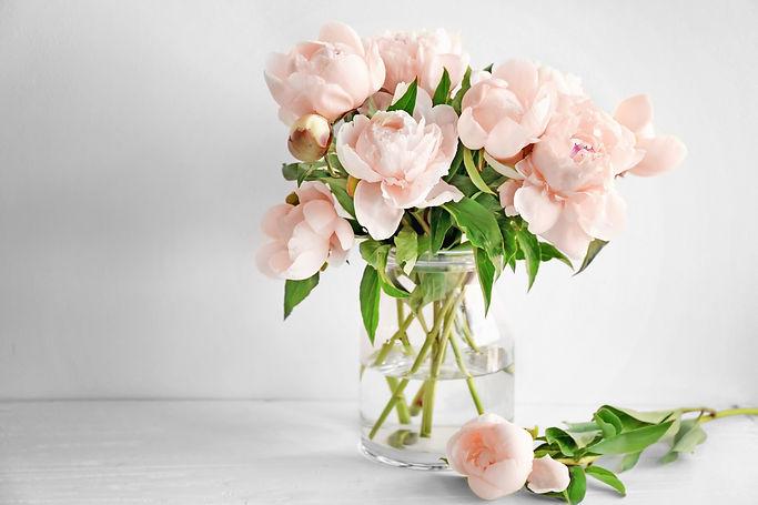 Vase with beautiful peony flowers on tab