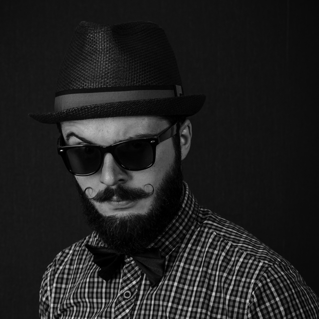 Bearded man with curly mustache and sunglasses