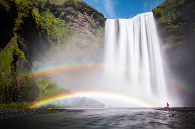 Hiker-and-double-rainbow-below-Skógafoss