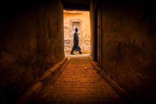Man-walking-past-narrow-alley-2,-Fes,-Mo