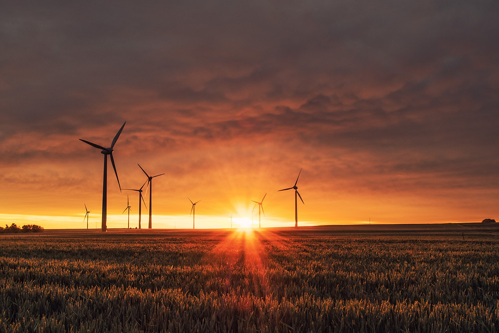 Renewable energy wind turbines at sunset. UK 2021 climate diplomacy presents political risks and opportunities.