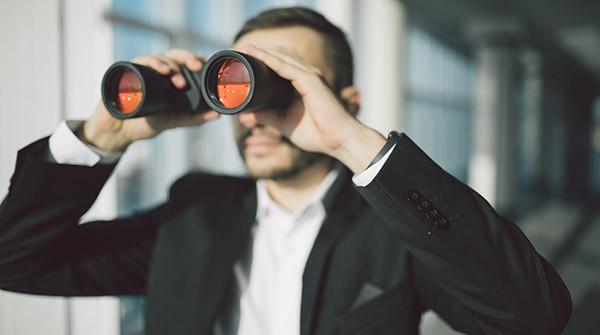 man looking at something with binoculars