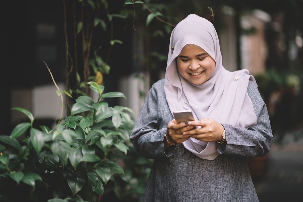 a young woman smiling at her phone