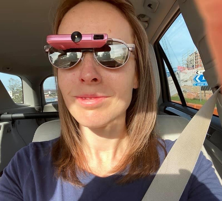 Lady with long brown hair sitting in a car wearing a pink bioptic telescope with glasses