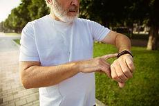 senior-man-as-runner-with-fitness-tracker-city-s-street-caucasian-male-model-using-gadgets