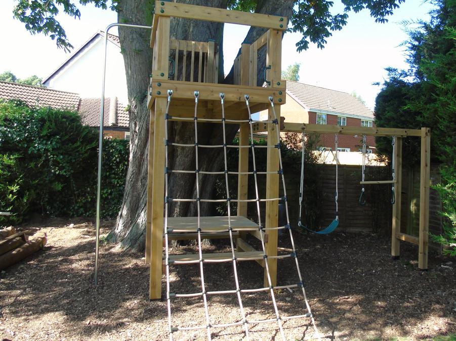 Play tower with climbing net, fireman's pole