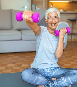 Lady with short grey hair and blue t-shirt and yoga pants on floor with exercise weights smiling.