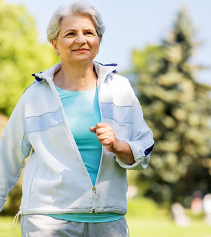 Lady with short grey hair in a jogging suit is walking briskly for healthy exercise.