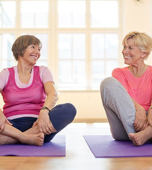 2 ladies sitting on purple yoga mats, legs crossed, smiling at each other, happy.