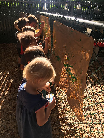 kids painting on a fence.JPG