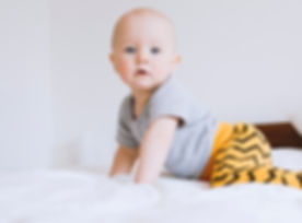 Infant on bed looking curious