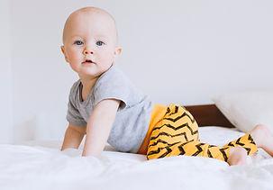 Bébé à quatre pattes sur un lit,portant un sarouel imprimé Jaune de la marque Koh mabby et un body gris simple regardant l'objectif