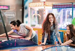 Three females playing arcade games