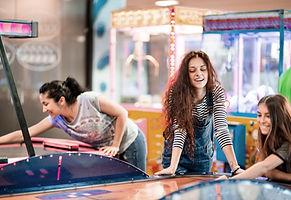 Three females playing arcade games