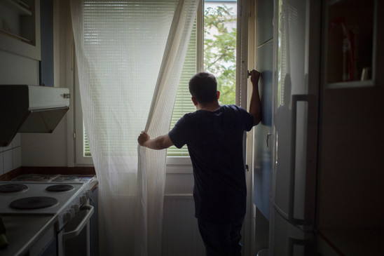 Alamin, 29, is looking out the window from a two room apartment in Jakobsberg on October 3, 2017 in Stockholm, Sweden. He shares it with six other people.