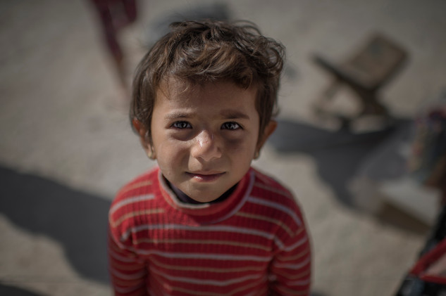 Jihan, 4, is quite, she is in the background of the other children in Suruc refugee camp, Turkey, April 25, 2016. She fled from Kobane with her family.