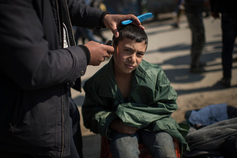 """Oday Awad, 9, gets a haircut by Mohammed Shian in the refugee camp in Idomeni, Greece, March 19, 2016.   """"I want to go to Germany. I have done surgery and need medicin. When i grow up i want to play football"""", says Oday Awad."""