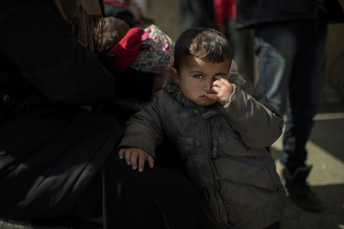 Mohammad, 2, is waiting with his pregnant mother by the hospital tents in the refugee camp in Idomeni, Greece, March 19, 2016.