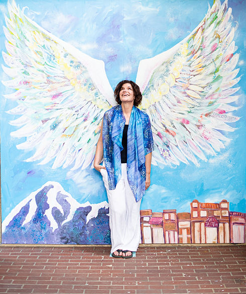 katie in front of a wall with angel's wings painted on it