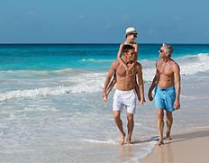 Three generations of men walking on the beach