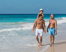 Three generations of men walking on the beach