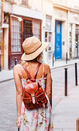 woman with travel backpack looking down the street