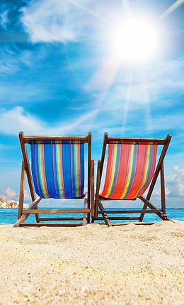 back of two beach chairs in the sun on the beach